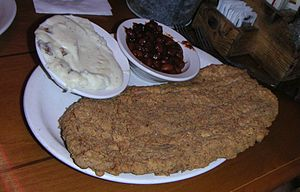 Chicken fried steak, served with mashed potatoes (topped with country gravy) and baked beans