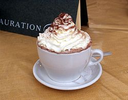 A cup of hot chocolate topped with whipped cream from a pressurized can