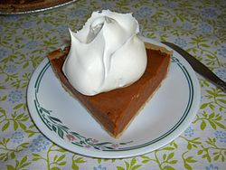 A slice of pumpkin pie topped with a whipped cream rose