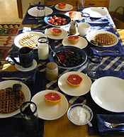 An example of a country breakfast in U.S. This includes waffles with fruit and sausage patties.