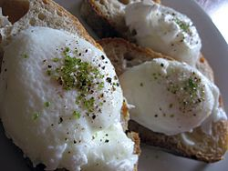 Poached eggs sprinkled with matcha and salt, served on sourdough bread.