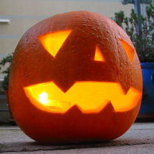 A jack-o'-lantern, made from a pumpkin, lit from within by a candle.