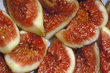 Fresh figs cut open showing the flesh and seeds inside