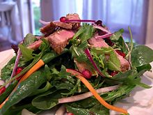 Green salad with roast beef, pomegranate vinaigrette, and lemon juice