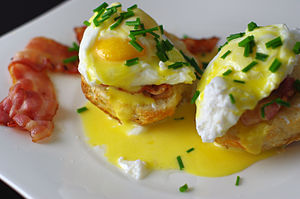 Eggs Benedict with a slice of bacon on the side.