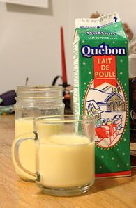 A carton and a glass of eggnog