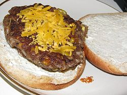 Veggie burger topped with grated cheese on a bun
