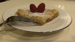 A slice of Gooey butter cake, garnished with powdered sugar and raspberries.