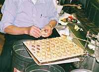Hot fortune cookies being folded around paper fortunes.
