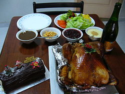 Roast turkey served with salad, sauces and sparkling juice. On the left is a log cake.