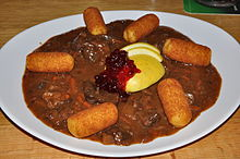 Venison goulash with apples, berries and potato croquettes