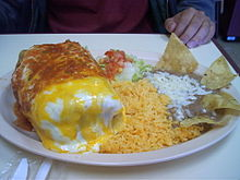 A chimichanga with refried beans and rice