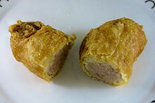 A battered sausage, sliced in half after cooking