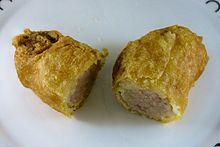 A battered sausage, sliced in half after cooking