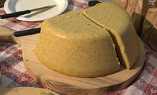 Polenta served in the traditional manner on a round wooden cutting board