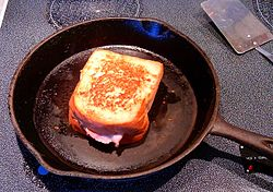 A grilled ham and cheese sandwich, in a cast iron frying pan