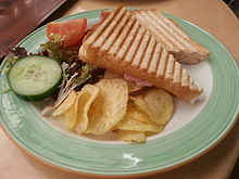 A grilled ham and cheese sandwich with a side of salad and chips/crisps