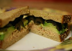 A tuna fish sandwich with black olives and avocado