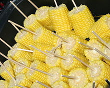 Cooked corn on the cob with serving sticks