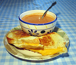 A grilled cheese sandwich with American cheese, served with tomato soup