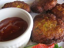 Fritters served with chili sauce in a ramekin
