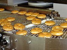 Glazed doughnuts rolling on a conveyor belt at a Krispy Kreme doughnut shop