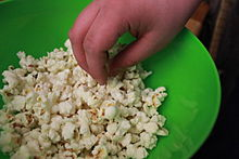 A person eating popcorn out of a bowl.