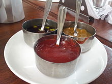 Tomato ketchup, accompanied with additional condiments