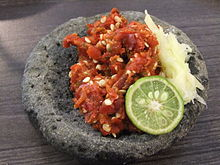 Traditional sambal terasi served on stone mortar with garlic and lime