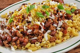 Chili mac prepared with macaroni noodles, chili, cheese, onion and green onion