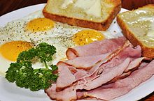 "Ham and eggs served with fried eggs prepared ""sunny side up"""