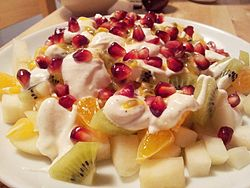 A plate of fruit salad made of pear, satsuma mandarin, kiwifruit, passion fruit, pomegranate seeds, and Greek yogurt mixed with honey, cardamom and vanilla sugar
