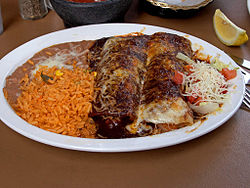 Enchiladas with mole sauce, served with refried beans and Spanish rice