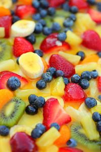 Fruit salad with kiwifruit, strawberries, blueberries, pineapples, bananas, and oranges.
