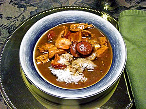 A bowl of shrimp, chicken and bacon gumbo, served over rice