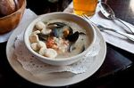 A cream-style seafood chowder at a restaurant, served with oyster crackers in the bowl atleft