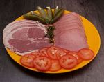 A tray of assorted lunch meats with pickles andtomatoes.