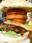 A steak burger with cheese and onionrings