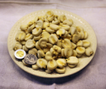 Dried (uncooked) form of hominy (US quarter and Mexican one-peso coins pictured for sizecomparison).