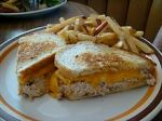 A tuna melt sandwich served with Frenchfries